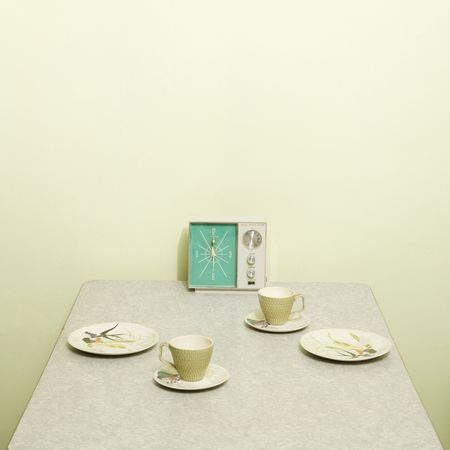 Retro 50s table setting with dishes coffee cups and vintage clock radio.