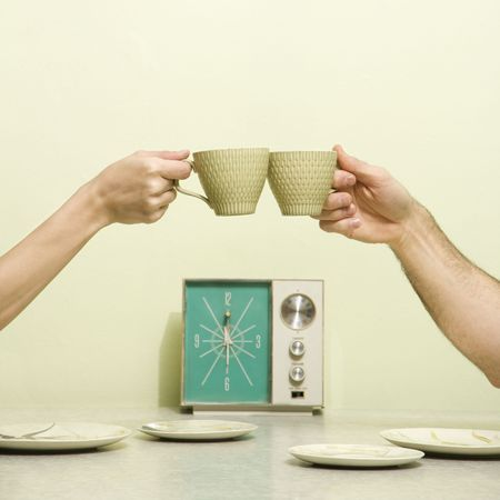 Caucasian male and female hands toasting with coffee cups across retro kitchen table setting. photo
