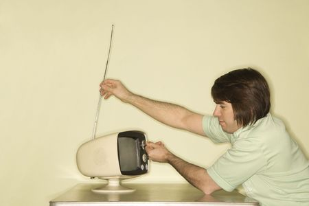 tune: Side view of Caucasian mid-adult man sitting at 50s retro dinette set adjusting old television antenna.