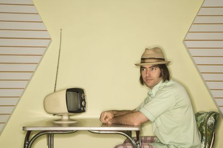 Caucasian mid-adult man wearing hat sitting at 50s retro dinette set in front of old television. photo