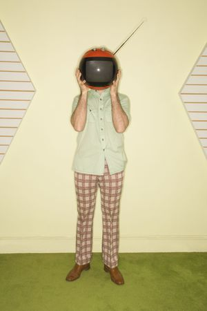 Caucasian mid-adult man wearing vintage clothing holding round red retro television in place of head. photo