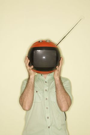 Caucasian mid-adult man holding round red retro television in place of head. photo