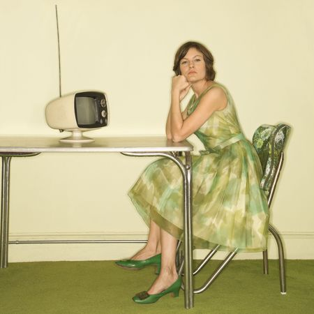 Pretty Caucasian mid-adult woman wearing green vintage dress sitting at 50s retro dinette in front of old televsion looking bored.
