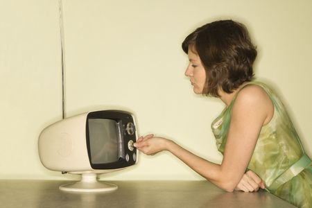 telly: Side view of pretty Caucasian mid-adult woman sitting at 50s retro dinette set turning old televsion knob.