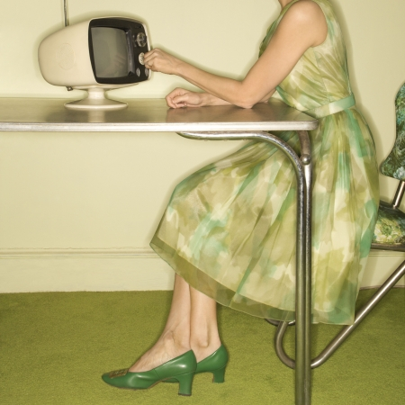 Side view of Caucasian mid-adult woman wearing green vintage dress sitting at 50s retro dinette set turning old televsion knob.
