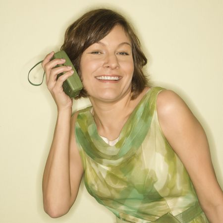 handheld: Pretty Caucasian mid-adult woman wearing green vintage dress holding handheld radio up to her ear and smiling at viewer. Stock Photo