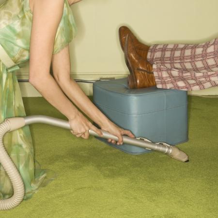 everyday scenes: Caucasica met�-adulto donna in ginocchio e vaccuuming tappeto attorno maschile piedi di riposo a piedi sgabello.  Archivio Fotografico