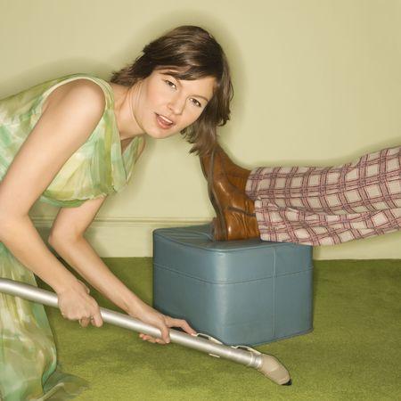donna in ginocchio: Piuttosto infelice caucasica met� donna adulta in ginocchio e vaccuuming tappeto nei pressi di sesso maschile piedi di riposo a piedi sgabello.  Archivio Fotografico