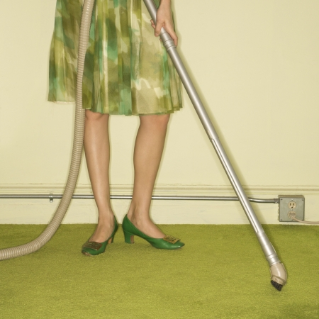 Close-up of Caucasian female legs with vacuum extension against green retro carpet. Stock Photo