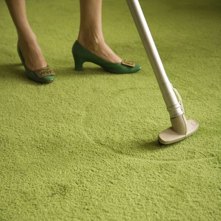 drudgery: Close-up of Caucasian female feet with vacuum extension against green retro carpet. Stock Photo