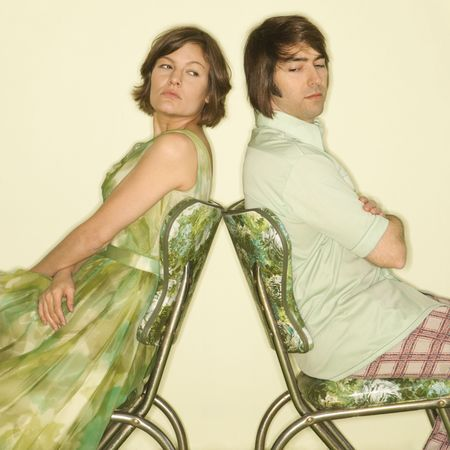 Caucasian mid-adult couple wearing vintage clothing sitting back to back in green vinyl chairs with arms crossed looking angry. photo
