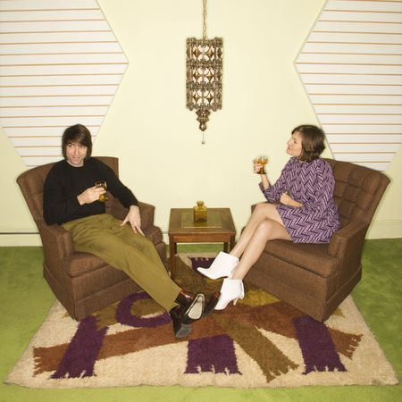 retro woman: Caucasian mid-adult man and woman wearing vintage clothing seated in brown retro chairs smiling and drinking.