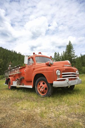antique fire truck: Low angle view of old vintage fire truck in field.