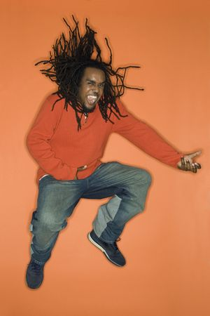 air guitar: African-American mid-adult man on orange background jumping while playing air guitar.