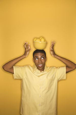 Young African-American man balancing bowl of lemons on his head on yellow background. photo