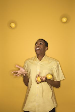 Young African-American man juggling lemons on yellow background. photo
