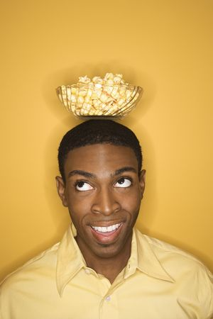 Young African-American man balancing bowl of popcorn on his head on yellow background. Stock Photo - 2219640