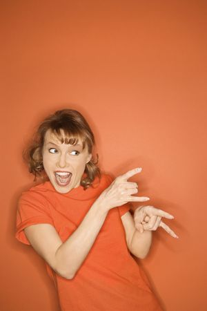 Smiling Caucasian mid-adult woman gesturing on orange background. Stock Photo - 2219735