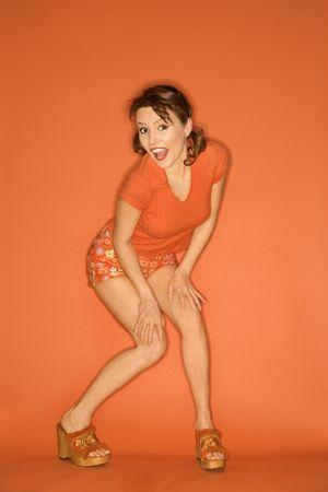 Caucasian mid-adult woman posing on orange background. Stock Photo - 2219706
