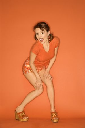 Caucasian mid-adult woman posing on orange background. Stock Photo - 2219706