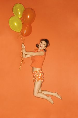 Caucasian mid-adult woman being lifted into the air by balloons, on orange background. Stock Photo - 2219590
