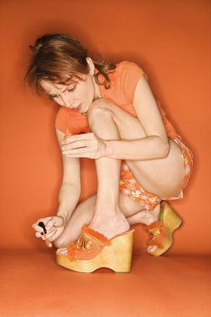 Caucasian mid-adult woman on orange background painting her toenails with nail polish. Stock Photo - 2219773