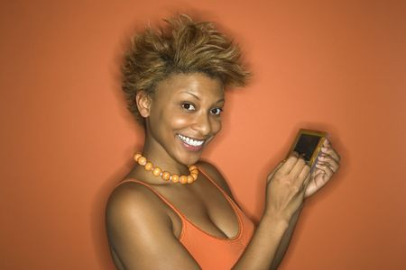 palmtop: Portrait of smiling young African-American adult woman on orange background using her palmtop computer.
