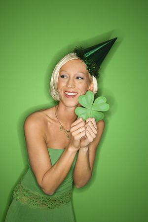 Portrait of smiling young adult Caucasian blond woman on green background wearing party hat and holding shamrock for Saint Patricks Day celebration. photo