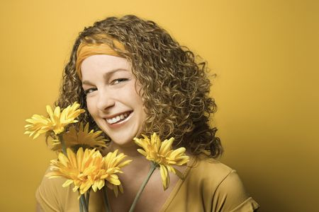 Portrait of smiling young adult Caucasian woman on yellow background holding bouquet of flowers. Stock Photo - 2219696