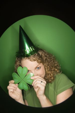Vignette of young adult Caucasian woman on green background wearing Saint Patricks Day hat and holding shamrock. photo
