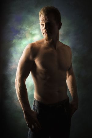 dramatically: Dramatically lit portrait of shirtless young adult Caucasian man on studio background.