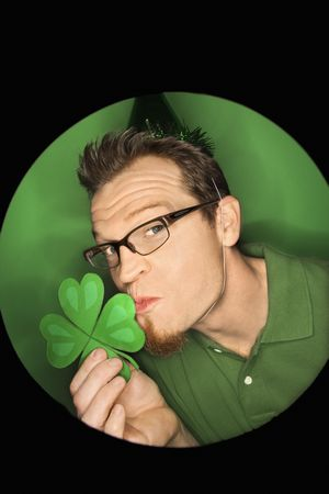 Vignette of adult Caucasian man on green background wearing Saint Patricks Day hat and kissing shamrock. photo