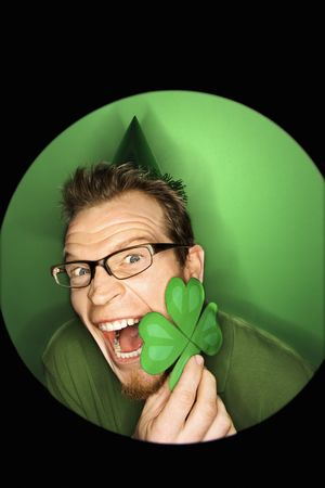 Vignette of excited adult Caucasian man on green background wearing Saint Patricks Day hat and holding shamrock. Stock Photo - 2219641