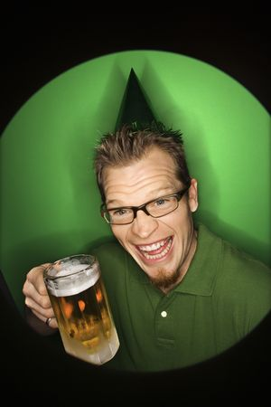 Vignette of adult Caucasian man on green background wearing green hat and holding beer. Stock Photo - 2219681