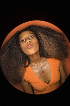 puckering lips: Vignette of young African-American adult woman with big hair and low cut dress on orange background puckering her lips. Stock Photo