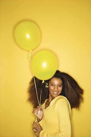 Portrait of smiling young African-American adult woman looking sweet on yellow background holding balloons. photo