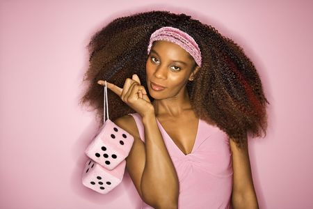 fuzzy: Portrait of smiling young African-American adult woman on pink background holding fuzzy dice. Stock Photo