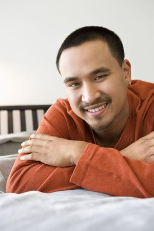 young adult man: Close-up of Asian young adult man lying on bed looking at viewer smiling.