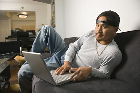 lounging: Asian young adult man wearing backwards baseball cap lounging on sofa working on laptop and looking at viewer. Stock Photo