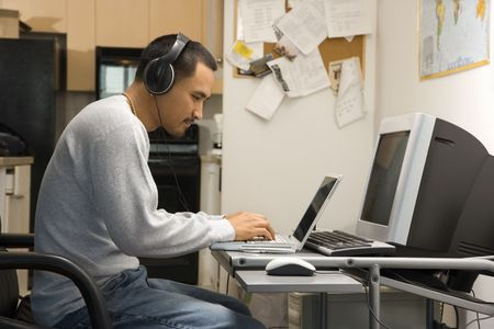young adult man: Side view of Asian young adult man sitting at desk typing on laptop wearing headphones.