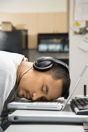 young adult man: Close-up of Asian young adult man sleeping with head on laptop keyboard and wearing headphones.