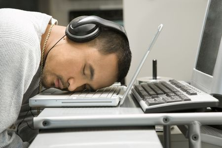 Close-up of Asian young adult man sleeping with head on laptop keyboard and wearing headphones. photo