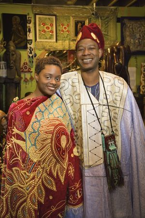 Portrait of smiling mid-adult African-American man and his young adult daughter wearing traditional African clothing. photo