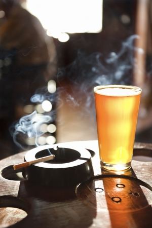 Full beer glass and cigarette with smoke rising in nightclub. photo
