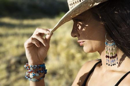 tipping: Close-up profile of mid-adult Caucasian woman tipping straw cowboy hat. Stock Photo