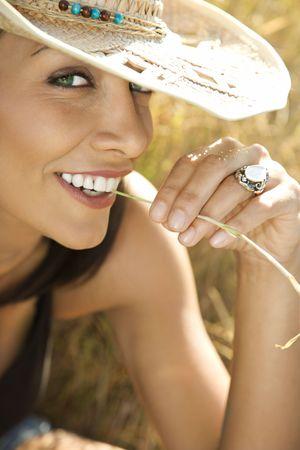 cappello cowboy: Primo piano del cappello e di masticare di cowboy da portare della paglia della donna caucasica dellmet� di-adulto sulla lamierina di erba.