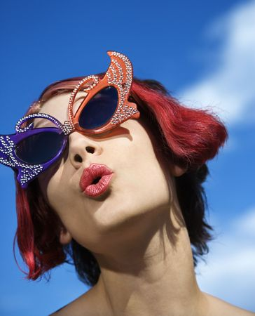 pucker: Close up of young adult Caucasian female wearing unique vintage glasses.
