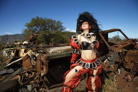 enact: Young adult Caucasian female dressed in pirate costume in junkyard.
