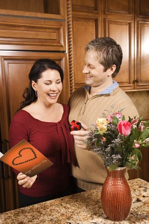 domiciles: Caucasian man giving Caucasian woman card, present and flowers.