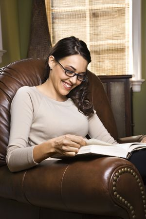 CaucasianHispanic young woman sitting in leather chair smiling and reading a book. photo